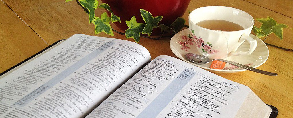 Bible on table with tea and ivy