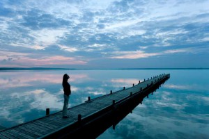 Lady walking on a dock at sunset