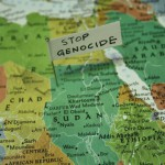 "Close up of map of africa with a note pined saying ""Stop Genocide"""