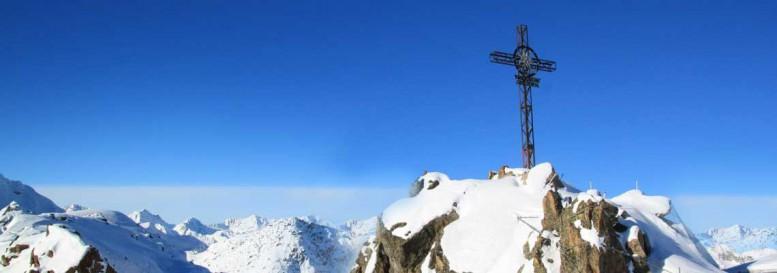 Christian cross on snow covered mountain peak.