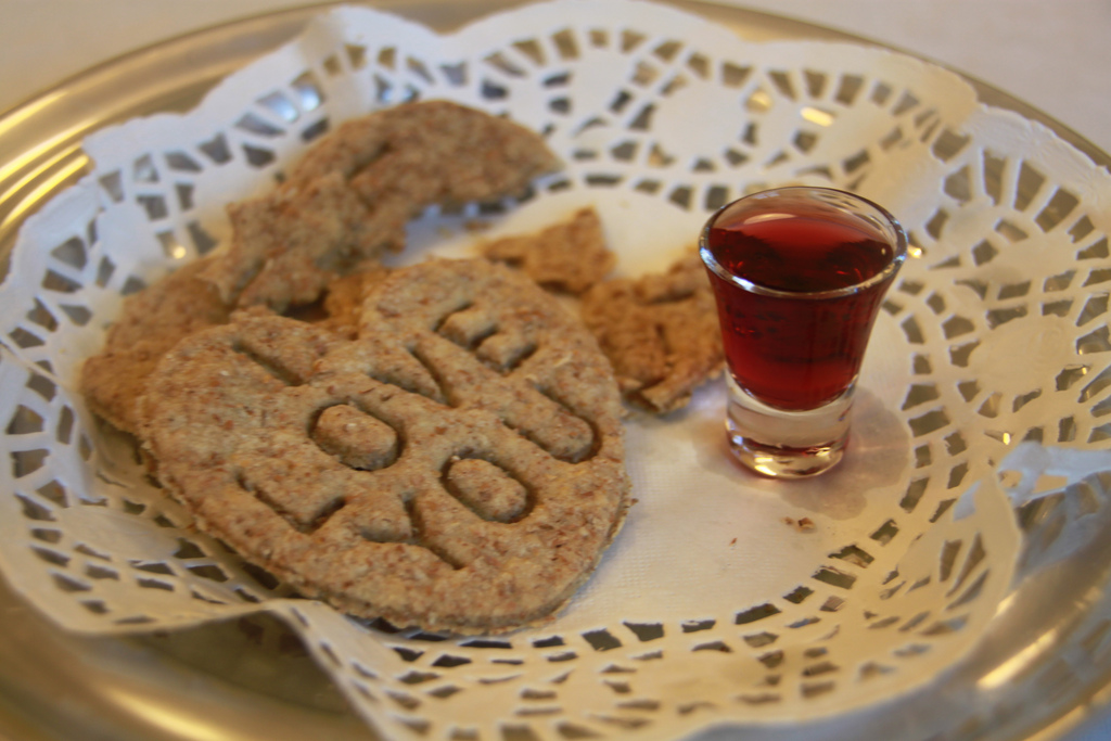 Heart shaped communion bread on lace with grape juice
